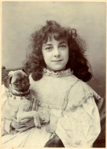 Vintage photograph of a cute victorian era girl and her pet dog circa 1880