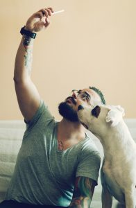 Cheerful man making selfie with his dog, american staffordshire terrier.